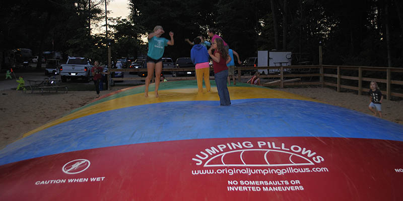 kids jumping on the jumping pillow having fun at gateway park campground in mi
